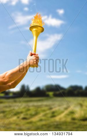 Low angle view of sportsman holding a cup against green field