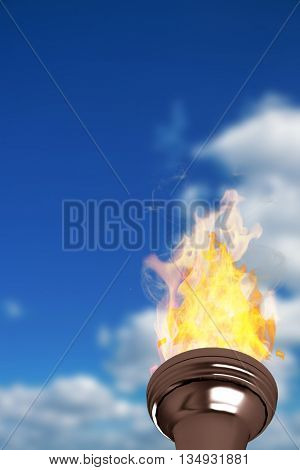 The olympic fire against low angle view of blue sky