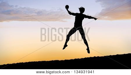 Female athlete with elbow pad throwing handball against clouds