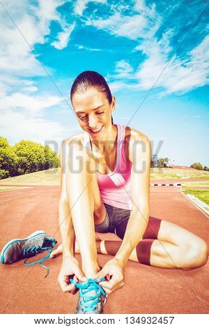 A sporty woman doing her shoelace against high angle view of track
