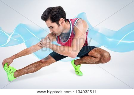 Male athlete stretching his hamstring against grey background