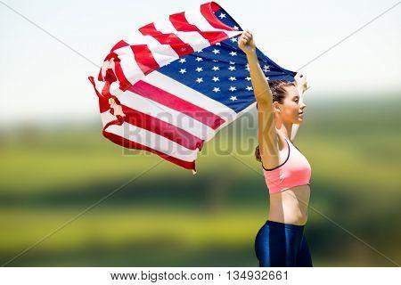 Profile view of sportswoman raising an american flag against scenic landscape