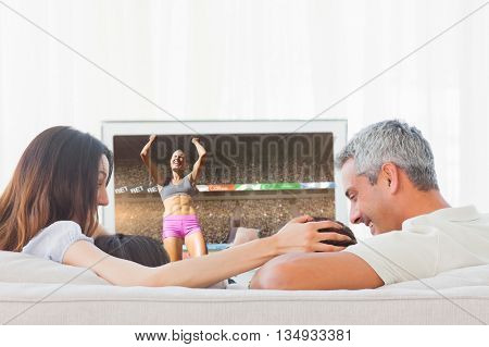 Low angle view of sportswoman celebrating her victory against family watching television together sitting on sofa
