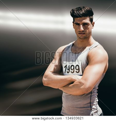 Portrait of handsome sportsman is posing with crossed arms against spotlight