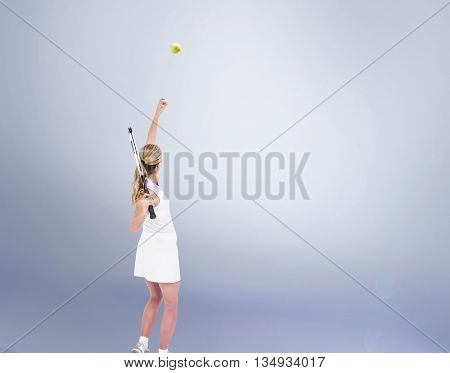 Athlete holding a tennis racquet ready to serve against grey vignette