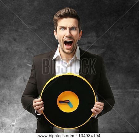 Man in black suit holding big clock on grey background