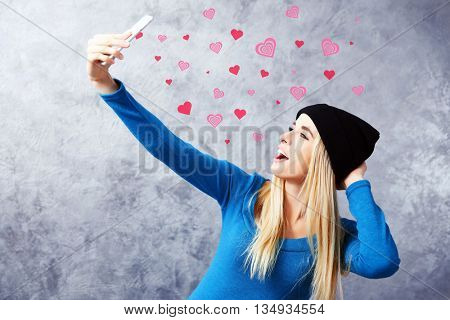 Young girl in black hat holding smart phone on grey wall background