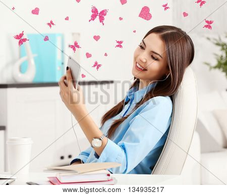 A beautiful successful woman with mobile phone sitting at the modern office
