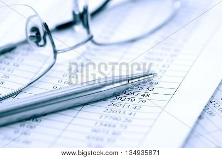 Business research. Closeup of spectacles and pen on paper with digits