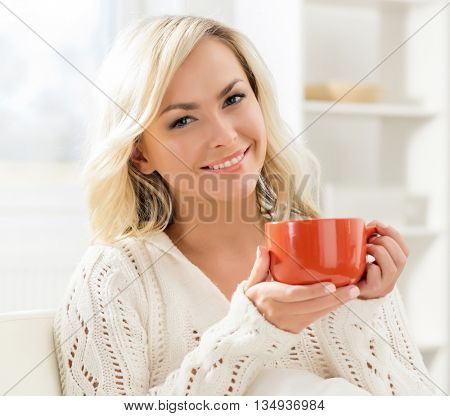Beautiful smiling woman enjoying the smell of coffee in the morning.