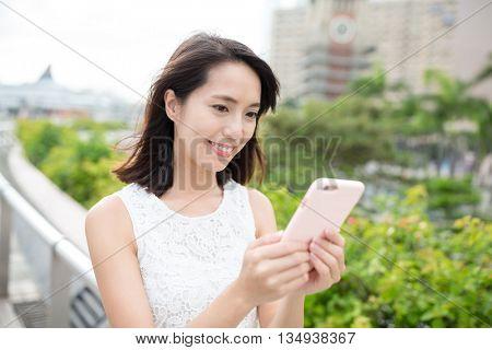 Woman use of smart phone with hong kong clock tower