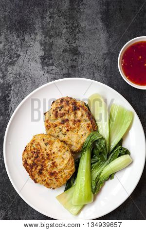 Thai chicken burgers with a sweet chili sauce and wilted Asian Greens.  Overhead view on slate.