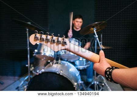 Guitar neck close-up on drum set background . Focus on guitar neck and guitar player hand, drummer playing on drums on background. Alive performance
