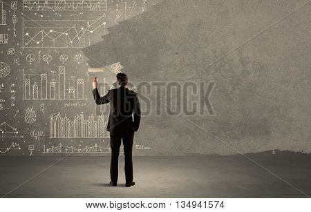 An elegant businessman covering pie charts, statistics, numbers, data, graphs on urban concrete wall with fresh paint using a roller concept