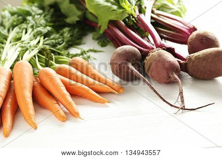 Fresh Beets And Carrots On A White Wooden Table