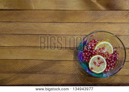 Transparent bowl full of lemon and garnet