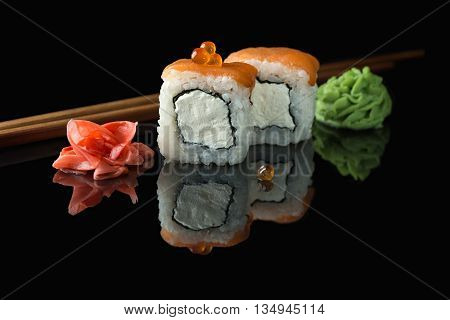 Philadelphia sushi rolls made of cream cheese inside and salmon outside decorated caviar. Pickled ginger wasabi and chopsticks. Isolated on a black background