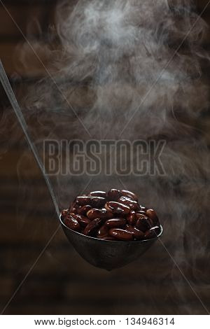 Cooked red kidney beans in a ladle with the effect of steam on a dark background