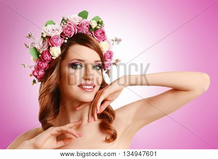 Beautiful young woman wearing floral headband on pink background