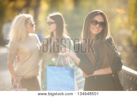 Beautiful slender young brunette woman with long straight hair,wearing a black light jacket,wearing dark sun glasses,posing in yellow autumn Park on a background of two friends,in the hands holding colorful paper shopping bags