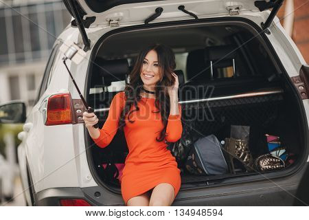 Slender,beautiful brunette woman with long curly hair and brown eyes,a beautiful smile,straight white teeth,wearing a orange dress,sitting alone on the trunk of a white car loaded with things,taking a selfie white smartphone outdoors in summer