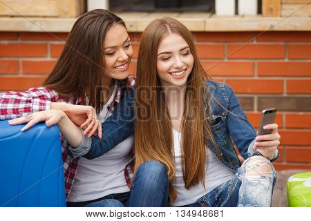 Cute girlfriend,two young women-a brunette with long straight hair,cute smile,dressed in blue jeans,a white t-shirt,plaid shirt and blue jacket,with blue and green suitcases sitting in front of the station and read a text message on smartphone