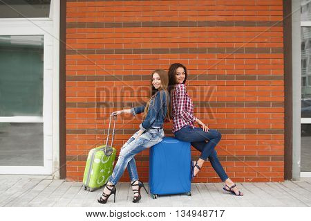 Funny girlfriend,two young women-a brunette with long straight hair,cute smile,dressed in blue jeans,a white t-shirt,plaid shirt and blue jacket,with blue and green suitcases sitting in front of the station on the blue suitcase