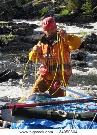 KOLA PENINSULA RUSSIA - AUGUST 11 - The man tied the rope to inflatable catamaran in Kola Peninsula on August 11 2008.