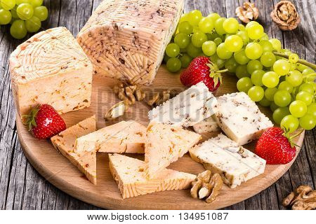 Cheese plate: organic homemade goat cheese with walnuts and spices. Green Grapes strawberry and walnuts on an old rustic background studio lights close-up