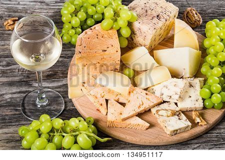 wineglass with cold white wine and Cheese plate: organic homemade goat cheese with walnuts and spices. Green Grapes and walnuts on an old rustic background studio lights close-up