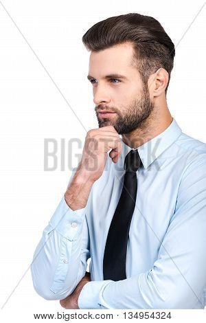 Lost in business thoughts. Thoughtful young handsome man in shirt and tie holding hand on chin and looking away while standing against white background