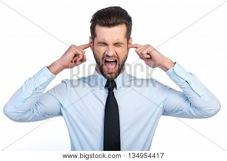 Too loud sound! Frustrated young man in shirt and tie covering ears with fingers and keeping eyes closed while standing against white background