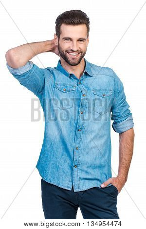 He got candid smile. Confident young handsome man in jeans shirt holding hand behind head and smiling while standing against white background
