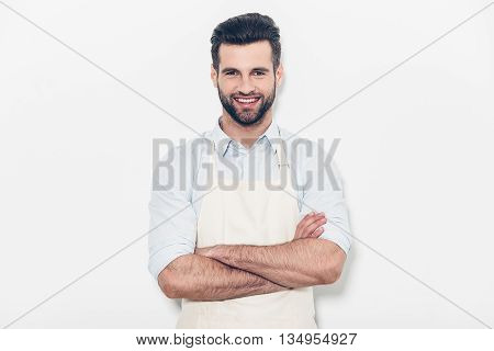 Man in apron. Confident young handsome man in apron keeping arms crossed and smiling while standing against white background