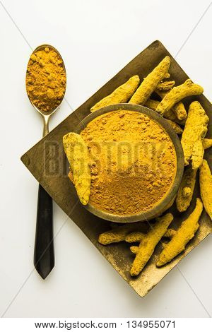 dry Turmeric and turmeric powder in square brass plate and brass bowl and a brass spoon