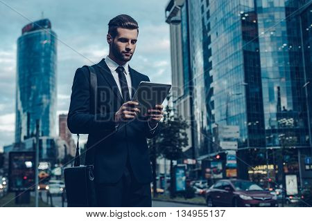 Modern businessman. Night time image of confident young man in full suit holding digital tablet and looking at it while standing outdoors with cityscape in the background
