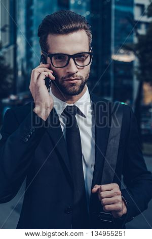 Confident businessman on the phone. Night time image of confident young man in full suit talking on the mobile phone and looking at camera while standing outdoors with cityscape in the background