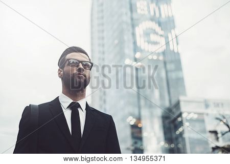 Businessman in city. Low angle view of confident young and handsome man in formalwear walking along the street with cityscape in the background