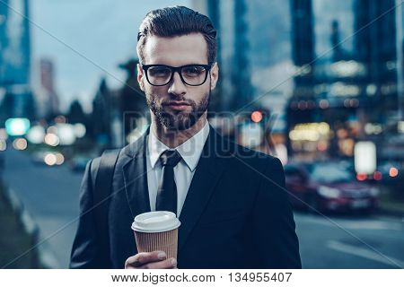 Enjoying best coffee in city. Night time image of confident young man in full suit holding coffee cup and looking at camera while standing outdoors with cityscape in the background