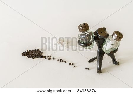 Vintage metal monkey figurine with pepper and salt shaker followed by the black peppercorns and sea salt.