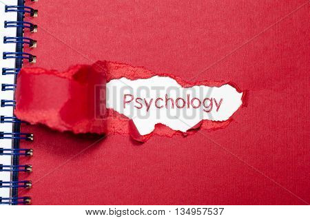 The word psychology appearing behind torn paper.