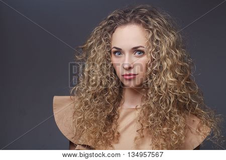 Beauty. Portrait of beautiful woman with curly hair on black background in studio