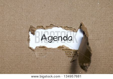 The word agenda appearing behind torn paper