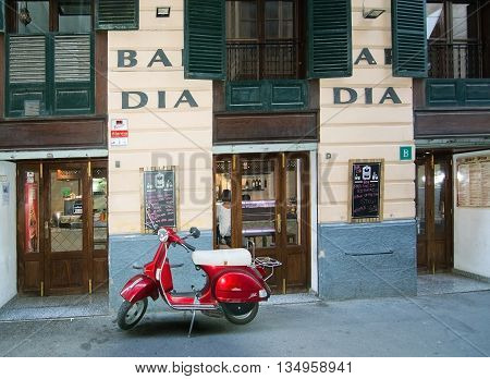 Red Vespa Scooter Parked In Front Of Bar Dia