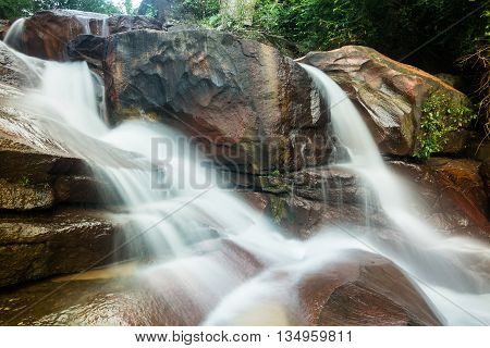 Cascading waterfall and red rock in Penang, Malaysia