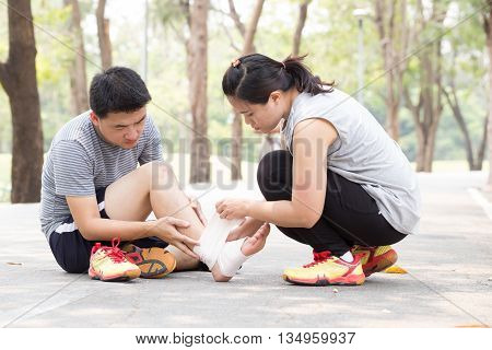 Sports injury. Man with twisted sprained ankle and getting help from woman bandaged ankle