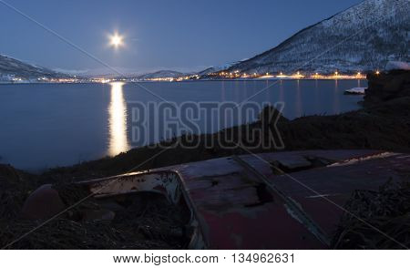 moon shining on wrecked boat at arctic coastline