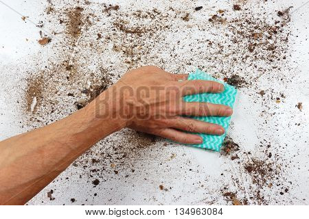 Hand with cloth cleans a very dirty surface
