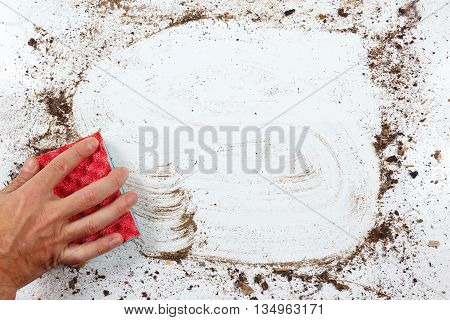 Hand with red sponge wiping a very dirty surface