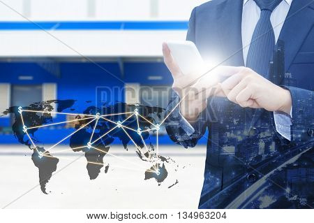Double exposure of businessman using smart phone network connection world map and city of business center with blurred cargo distribution warehouse background international transportation trading business concept